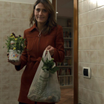 The lawyer enters her kitchen with the vegetables she bought and the pansies that will be used to garnish the dish