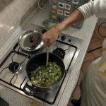 The vegetables are slowly cooking in a pan while she stirs them