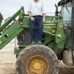 Juan Manuel Priego Gómez standing on a tractor wheel